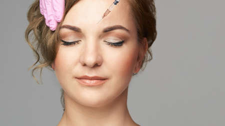 Face needle injection. Young woman cosmetology procedure. Doctor gloves. Wrinkles. 免版税图像