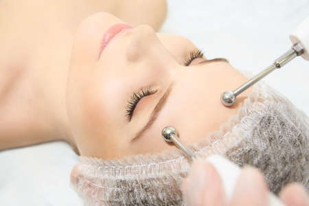 Microcurrent facial dermatology procedure. Model. Aesthetic radiofrequency treatment. Micro current cosmetology massage.