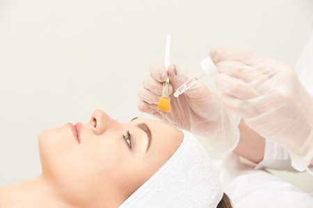 Giovane donna che pulisce la pelle del viso in salone. Buccia di retinolo con pennello. Peeling organico acido. Archivio Fotografico