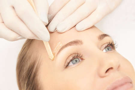 Zuckerhaarentfernung vom Körper der Frau. Wachsepilation Spa-Verfahren. Verfahren Kosmetikerin weiblich. Augenbraue.