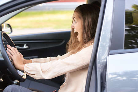 Young woman in car. Ride instruction accident. Automobile loan.