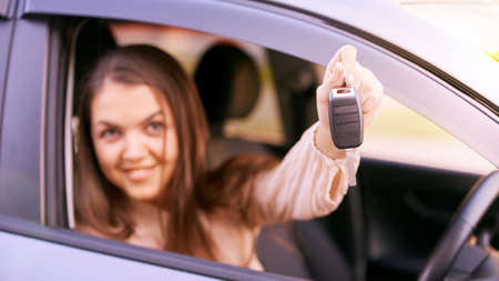 Young woman in car. Ride instruction. Automobile loan. Hand with key.