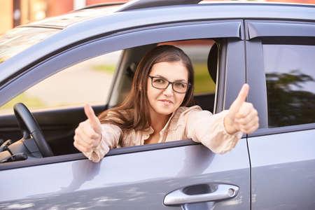 Mujer joven en coche. Instrucción de conducción. Préstamo de automóvil.