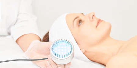 Skincare cosmetology facial procedure. Beauty woman face. Blue light medical therapy. Specialist hand.