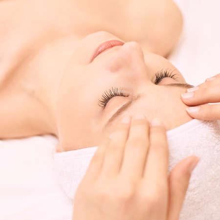 Ragazza di bellezza che ottiene massaggio facciale al salone. Asciugamano bianco. Mani di persone. Occhi chiusi.
