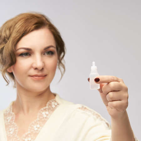 Woman apply eye drops. Girl glaucoma treatment.