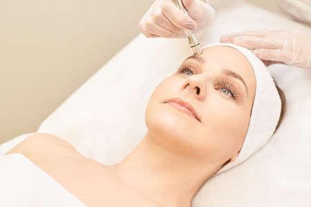 Soin du visage en cosmétologie. Jeune fille patiente. Matériel cosmétique de salon. Nettoyage de la peau du diamant dermatologique.