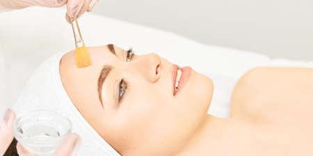 Facial brush peel retinol treatment. Beauty woman peeling procedure. Cosmetology young girl therapy.Hyaluronic acid. Foto de archivo