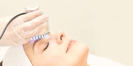 Light infrared therapy. Cosmetology head procedure. Beauty woman face. Cosmetic salon device. Facial skin rejuvenation. Archivio Fotografico - 125518302