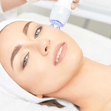 Light infrared therapy. Cosmetology head procedure. Beauty woman face. Cosmetic salon device. Facial skin rejuvenation. Фото со стока