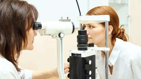 Examen de oftalmólogo ocular. Recuperación de la vista. Concepto de comprobación de astigmatismo. Dispositivo diagmostico oftalmologico. Retrato de niña de belleza en la clínica. Foto de archivo