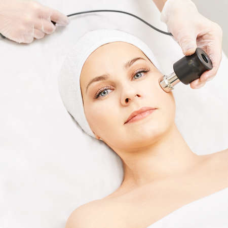 Electroporation woman face treatment. Facial rejuvenation therapy. Cosmetology skin spa equipment. Rf lifting. Massage device. Imagens