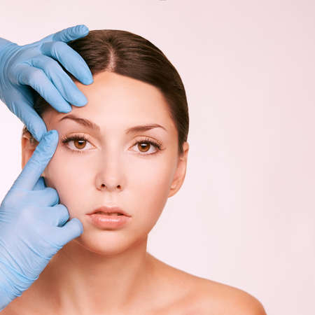 Female derma rejuvenate treatment. Doctor in gloves touch woman face. Cosmetology pretty portrait. Facial injection patient. 스톡 콘텐츠
