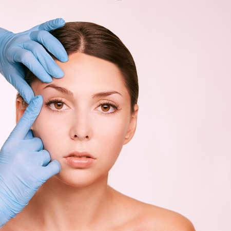 Female derma rejuvenate treatment. Doctor in gloves touch woman face. Cosmetology pretty portrait. Facial injection patient. Banco de Imagens