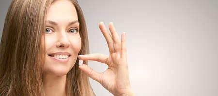 Girl take white pill. Human drink painkiller. Anti headache supplement. Mature woman. Standard-Bild