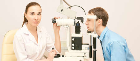 Eye ophthalmologist exam. Eyesight recovery. Astigmatism check concept. Ophthalmology diagmostic device. Beauty girl portrait in clinic. Man patient. Stock Photo
