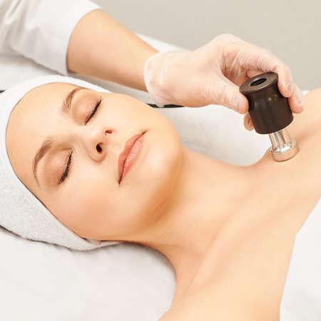 Mesoterapia senza iniezione. Medico e paziente in clinica. Strumento di cosmetologia di ringiovanimento. Procedura estetica del viso della pelle della donna. Antirughe dal lifting.