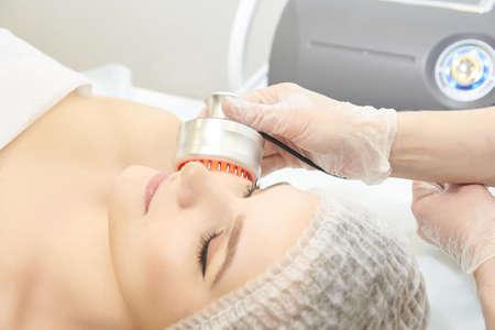 Light infrared therapy. Cosmetology head procedure. Beauty woman face. Cosmetic salon device. Facial skin rejuvenation. Archivio Fotografico - 125518580