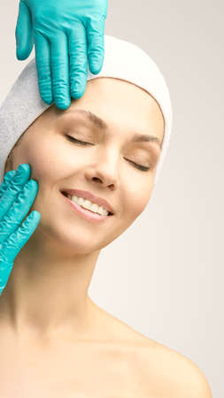 Female derma rejuvenate treatment. Doctor in gloves touch woman face. Cosmetology pretty portrait. Facial injection patient. Stok Fotoğraf