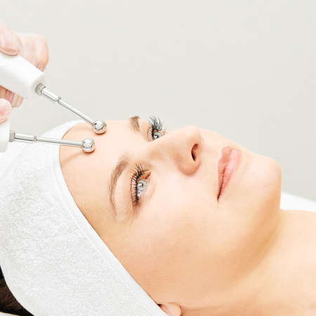 Microcurrent esthetics procedure. Beauty girl face. Cosmetology machine. Doctor hands. Two micro balls. Wrinkle reduction.