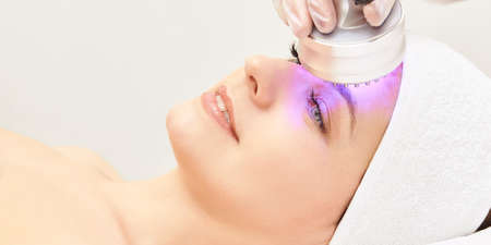 Light infrared therapy. Cosmetology head procedure. Beauty woman face. Cosmetic salon device. Facial skin rejuvenation. Stok Fotoğraf