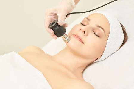 Gesichtsverjüngung durch Elektroporation. Kosmetik Gesicht Behandlung. Kosmetik-Hardware für den Salon. Medizinische Frauenausrüstung. Schönes Mädchen.