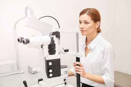 Eye ophthalmologist exam. Eyesight recovery. Astigmatism check concept. Ophthalmology diagmostic device. Beauty girl portrait in clinic. Stock Photo