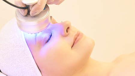 Light infrared therapy. Cosmetology head procedure. Beauty woman face. Cosmetic salon device. Facial skin rejuvenation. Reklamní fotografie