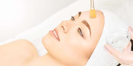 Gesichtsbürstenpeeling Retinol-Behandlung. Schönheitsfrauenpeelingverfahren. Kosmetologie junges Mädchen Therapie. Hyaluronsäure.