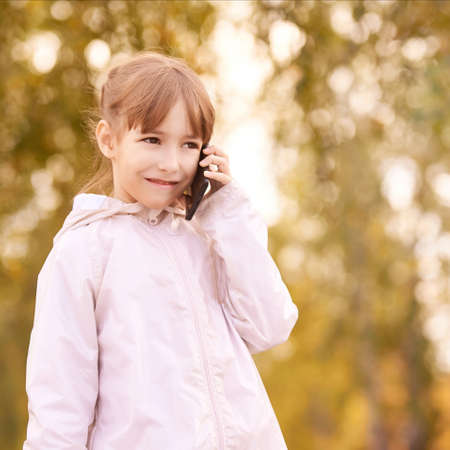 Young happy girl talks cellphone. Phone roaming. People with smartphone. Autumn background. Фото со стока