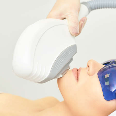 Anti acne removal procedure. Cosmetology device. Woman facial tightening clinic. Beautiful girl and doctor hand. 写真素材