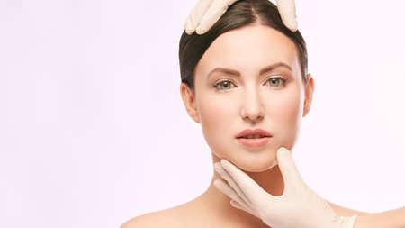Trattamento di ringiovanimento del derma femminile. Il dottore in guanti tocca il viso della donna. Ritratto grazioso di cosmetologia. Paziente con iniezione facciale. Archivio Fotografico