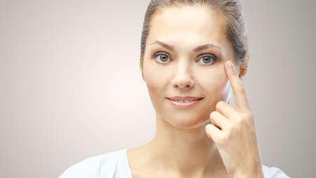 Woman point at dermatology skin problem. Cosmetology beauty girl portrait. Face care procedure. Stock fotó