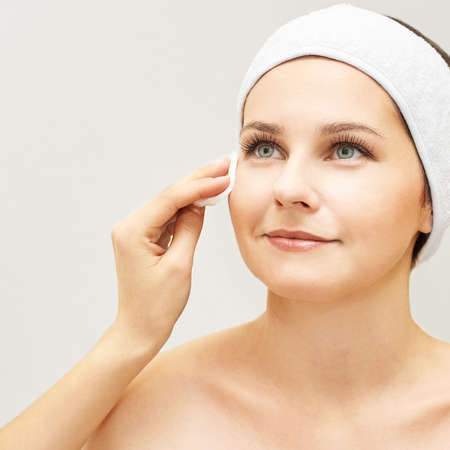 Cosmetology doctor remove mascara from girl face. Cotton pad with woman hands. Demakeup lotion. Reklamní fotografie