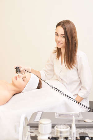 Non injection mesotherapy. Doctor and patient in clinic. Rejuvenation cosmetology tool. Woman aesthetic skin face procedure. Anti wrinkle fr lifting.