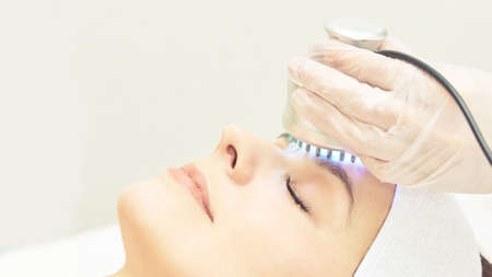 Light infrared therapy. Cosmetology head procedure. Beauty woman face. Cosmetic salon device. Facial skin rejuvenation. 免版税图像