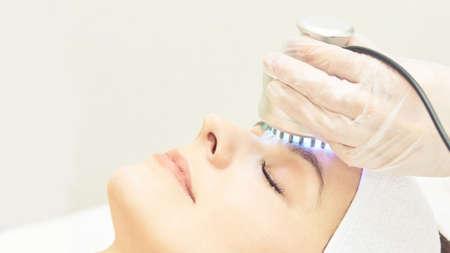 Terapia de luz infrarroja. Procedimiento de cabeza de cosmetología. Rostro de mujer de belleza. Dispositivo de salón cosmético. Rejuvenecimiento de la piel del rostro.