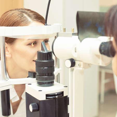 Examen de oftalmólogo ocular. Recuperación de la vista. Concepto de comprobación de astigmatismo. Dispositivo diagmostico oftalmologico. Retrato de niña de belleza en la clínica.