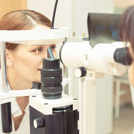 Eye ophthalmologist exam. Eyesight recovery. Astigmatism check concept. Ophthalmology diagmostic device. Beauty girl portrait in clinic.