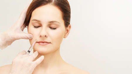 Woman face cosmetology treatment. Biorevitalization skin therapy. Doctor insert filler. Girl clinic facial mesotherapy. Injecting in medical salon.