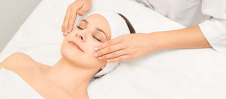 Face professional massage. Spa skincare treatment. Health facial masseur. Girl with doctor hands. Relax cosmetology procedure. Фото со стока - 131841513