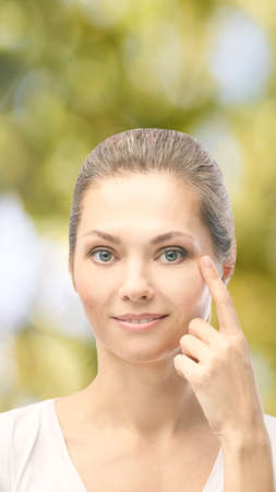Woman point at dermatology skin problem. Cosmetology beauty girl portrait. Face care procedure. Stock Photo