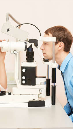 Eye ophthalmologist exam. Eyesight recovery. Astigmatism check concept. Ophthalmology diagmostic device. Beauty girl portrait in clinic. Man patient. Zdjęcie Seryjne - 131841719