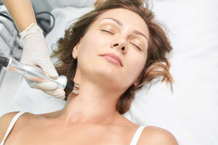 Dermatology skin care facial therapy. Medical spa anto wrinkles procedure. Woman face rejuvenation. Pretty girl. Rf cosmetician equipment. Chin and neck.