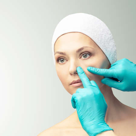 Female derma rejuvenate treatment. Doctor in gloves touch woman face. Cosmetology pretty portrait. Facial nosr injection patient. Zdjęcie Seryjne - 131842078