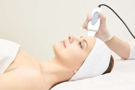 Ultrasinic cosmetology face equipment. Facial skin cleaning. Beauty female girl. Medical salon care machine.