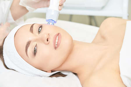 Light infrared therapy. Cosmetology head procedure. Beauty woman face. Cosmetic salon device. Facial skin rejuvenation. Stock fotó