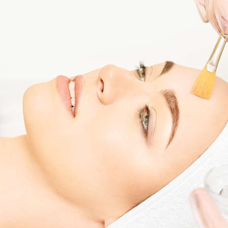 Trattamento al retinolo per peeling con spazzola per il viso. Procedura di peeling della donna di bellezza. Cosmetologia giovane ragazza terapia.Acido ialuronico.