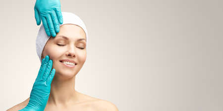 Female derma rejuvenate treatment. Doctor in gloves touch woman face. Cosmetology pretty portrait. Facial injection patient. Zdjęcie Seryjne - 131842115