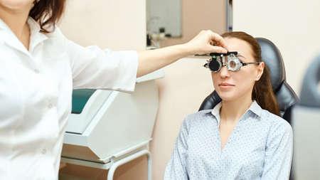 Egzamin okulistyczny oka. Odzyskiwanie wzroku. Koncepcja kontroli astygmatyzmu. Urządzenie diagnostyczne okulistyczne. Piękna dziewczyna portret w klinice. Zdjęcie Seryjne